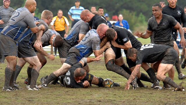 Men have a rugby tackle in the mud
